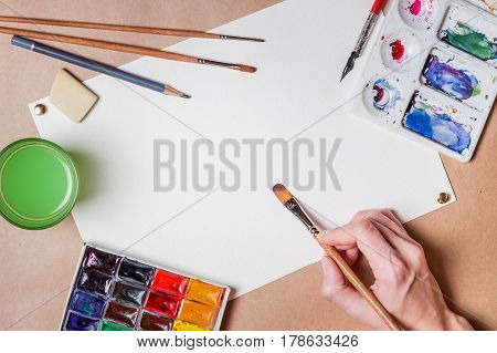 hand with brush painting with watercolor and blank white paper sheet
