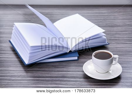 Book and cup of coffee on wooden table