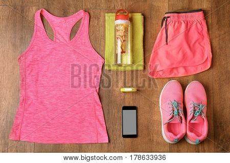 Fitness tracker and sports clothing on wooden floor, top view