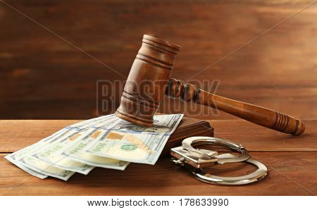Judge's gavel, handcuffs and money on wooden background