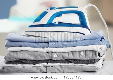 Electric iron and pile of clothes on blurred background