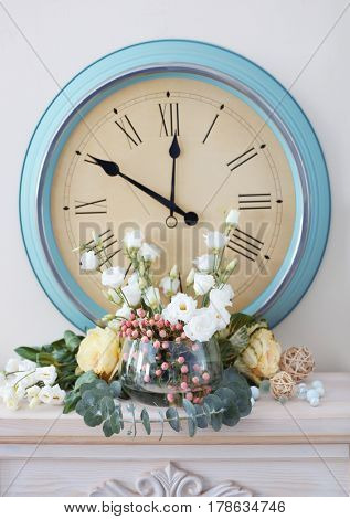 Beautiful composition with fresh flowers and vintage clock