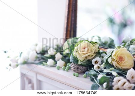 Beautiful fresh flowers lying near mirror, closeup