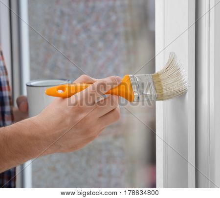 Hand of young man painting window in office