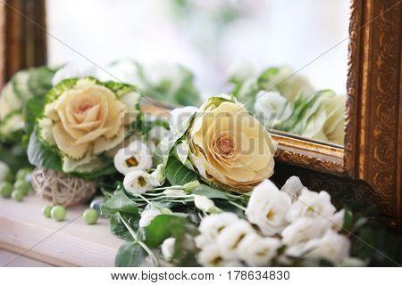 Beautiful fresh flowers lying near mirror, closeup