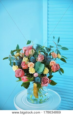 Glass vase with beautiful bouquet on color background