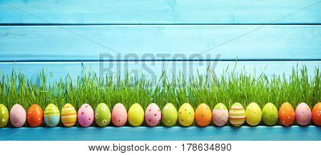 Easter eggs and green grass on wooden background