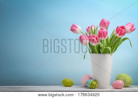 Spring easter tulips in bucket on blue background