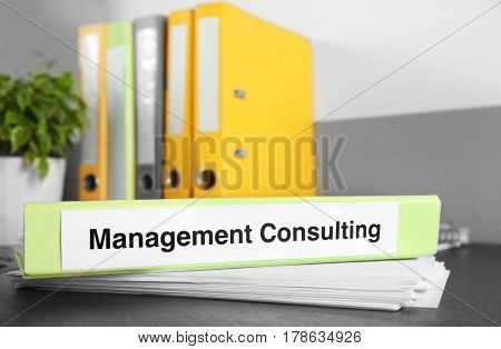 Folder with label MANAGEMENT CONSULTING on wooden table