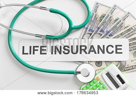 Life insurance concept. Calculator, stethoscope and banknotes on light background