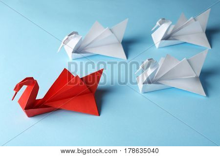 Boss vs Leader concept. White origami birds behind red one on blue background