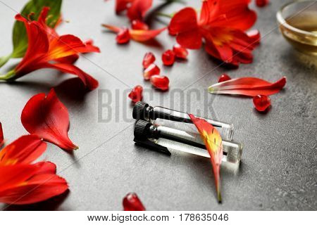 Beautiful composition with perfume samples and flowers on gray background
