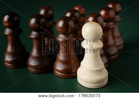 Boss vs Leader concept. Chess pieces on green background