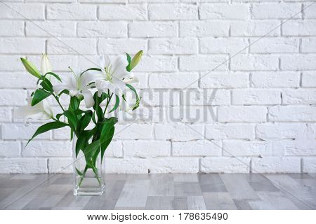 Vase with beautiful white lilies on brick wall background