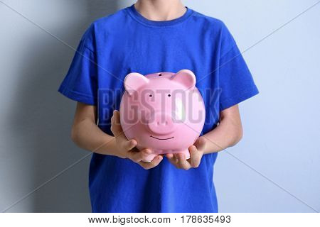 Cute child with piggy bank on color background, closeup