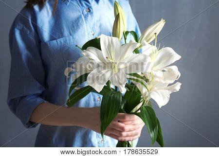 Woman holding beautiful white lilies, closeup