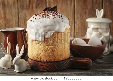Easter cake and bowl with eggs on wooden background