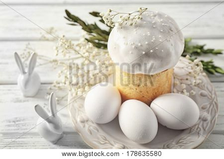 Decorated plate with Easter cake and eggs on wooden table