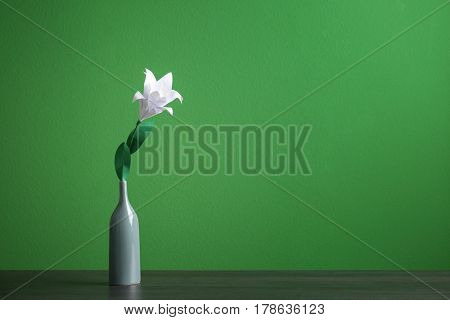 Vase with beautiful paper lily on wooden table