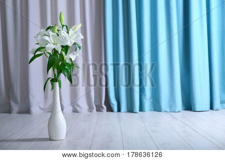 Beautiful white lilies in vase on floor