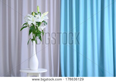 Beautiful white lilies in vase on curtain background