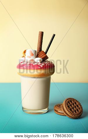 Milkshake, donut and other sweets in glass on color background