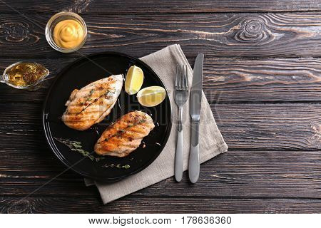 Plate with delicious chicken breasts and  lime on table