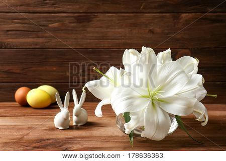 Beautiful composition with white lilies and Easter bunnies on wooden background