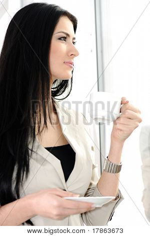 Young pretty female model drinking coffee inside the office, beside the glass window