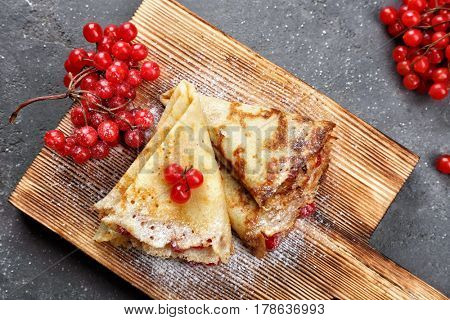 Delicious pancakes with viburnum on wooden board