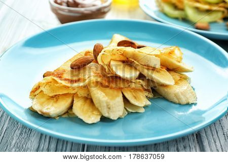 Blue plate with delicious pancakes on wooden table