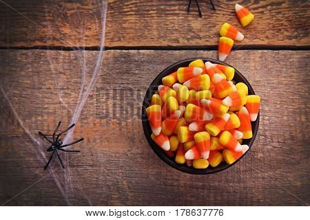 Bowl with tasty Halloween candies on wooden background