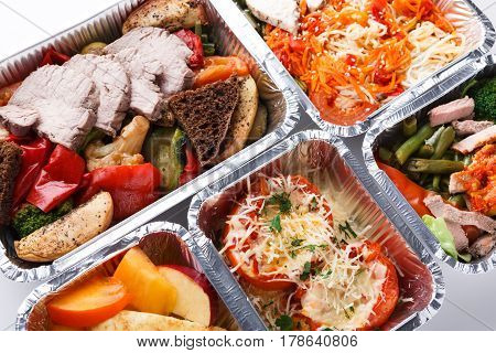 Healthy restaurant food background. Eating right concept. Fresh diet daily meals delivery. Fitness nutrition, vegetables, meat and fruits in foil boxes on wood