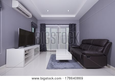 residential interior of modern living room with black sofa and TV