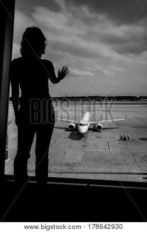 The silhouette of an unrecognizable person near large window at the airport. Plane in the background.
