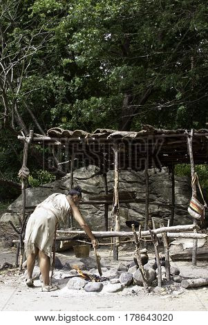 Plimoth Plantation, Plymouth, Massachusetts - September 10, 2014 - Wide view of a Wampanoag Indian woman tending her fire to heat a cauldron and bucket at Plimoth Plantation a large boulder and foliage in the background on a sunny day