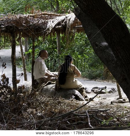 Plimoth Plantation, Plymouth, Massachusetts - September 10, 2014 - Squared close up of two Wampanoag Indian guides sitting under a hand build cover shelter awaiting tourists in the Wampanoag Indian Village at Plimoth Plantation surrounded by trees and fol