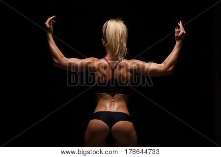 Beautiful athletic woman in sporty cloths is posing, holding hands up and showing her perfect body, back view isolated on dark background with copyspace.