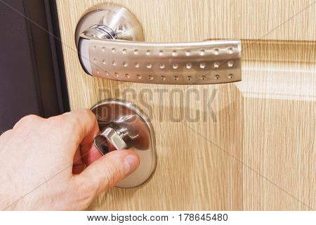 The man's hand closes the lock on the door. Turn the door latch. The concept of home security. Close all doors to the lock.