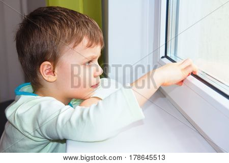 A little boy sits by the window and looks into the distance. The boy was thinking about the window, looking ahead. A child's view.