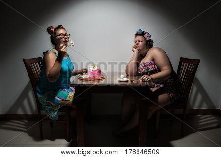 Portrait of beautiful plus size curly red hair young woman with egg, looking at her girlfriend, which eating sweet cake at the table