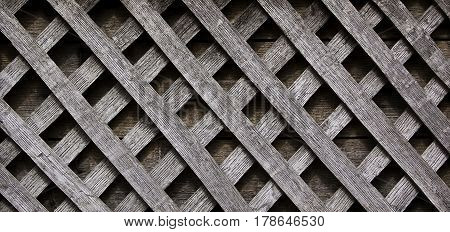 Close up of very old weathered lattice wood pattern excellent background or texture at Plimoth Plantation, Plymouth, Massachusetts, on a bright sunny day in September.