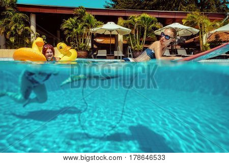 Beautiful young fat woman relaxing in the pool with yellow duck lifebuoy and thin amazing Lady lying on the surfboard