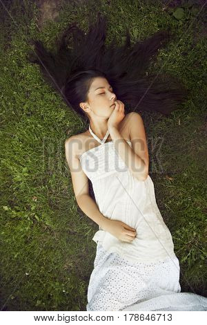 A girl with long dark hair wearing lying on grass