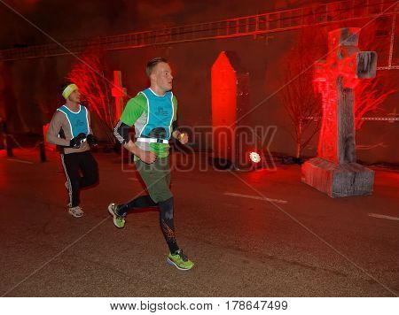 STOCKHOLM SWEDEN - MAR 25 2017: Two men running in a tunnel with red light and grave stones the Stockholm Tunnel Run Citybanan 2017. March 25 2017 in Stockholm Sweden