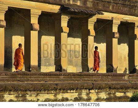 Siem Reap, Cambodia - Circa December 2011 - A shot of buddhist monks in reddish yellow robes walking along the corridor in one of the buildings in Angkor Wat
