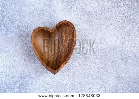 Wooden bowl in the shape of heart on a concrete background.