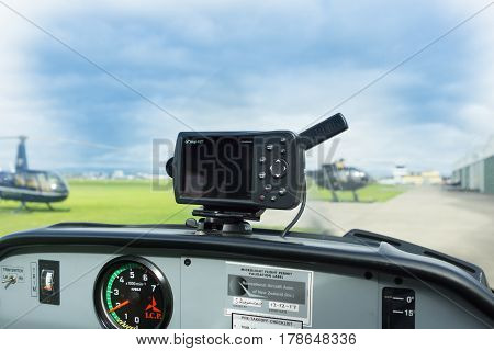 From the cokpit of small aircraft part of airfield with parked helicopters defocused through windscreen.