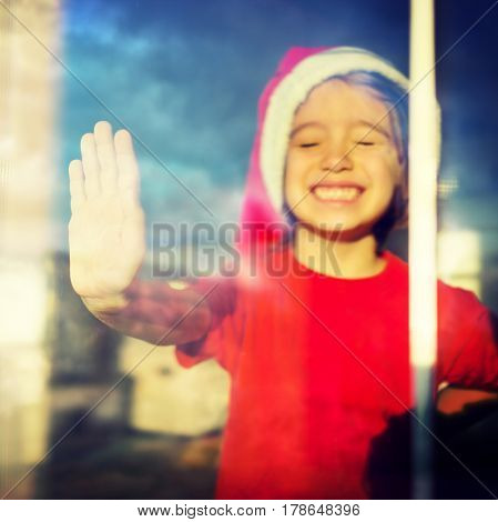 Little boy on window with hand on glass