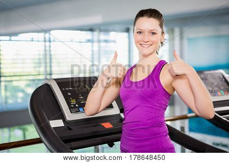 Smiling brunette with thumbs up standing on treadmill in the gym
